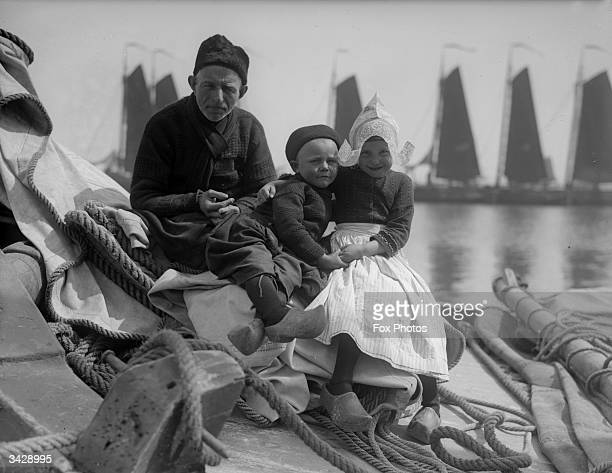 Two children and an old man sitting on a pile of sailing tackle by the sea in Volendam near Edam in the western Netherlands The little girl is...