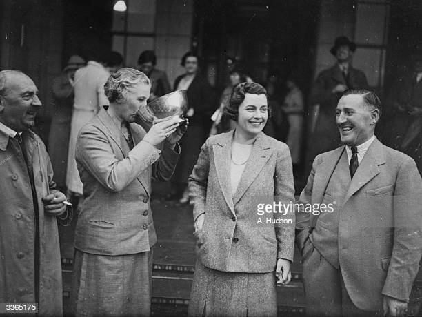Captain of the American amateur ladies golf team Glenna Collett smiles as British captain Doris Chambers drinks from the Curtis Cup Match trophy The...