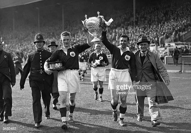 Harold Thomas and captain Gus Risman celebrate with the trophy after Salford beat Barrow to win the Rugby League Challenge Cup at Wembley. Bert Day...