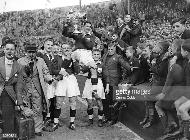 Team Captain Gus Risman is chaired by teammates with the trophy after Salford beat Barrow to win the Rugby League Challenge Cup at Wembley Stadium