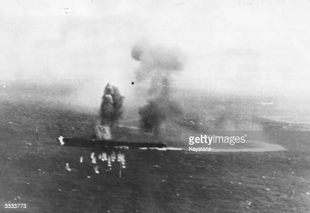 Burning Japanese aircraft carrier Shokaku takes evasive action to avoid American bombs during the Battle of the Coral Sea. The line of her wake shows...