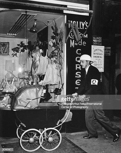 A time of great optimism and lingering doubt An airraid warden pushing his baby through Times Square New York Photo by Weegee/International Center of...