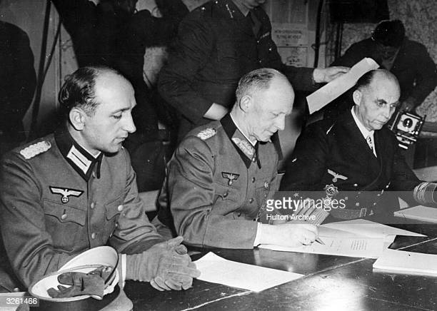 German soldier and Chief of the Operations Staff Alfred Jodl flanked by his aide on the left and Grand Admiral Hans Georg von Friedeburg on the right...