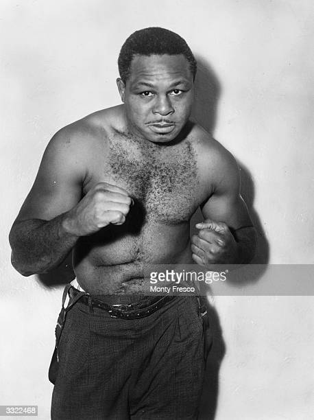 World lightheavyweight boxing champion Archie Moore spars for thecamera when in London for a championship fight against Yolande Pompey
