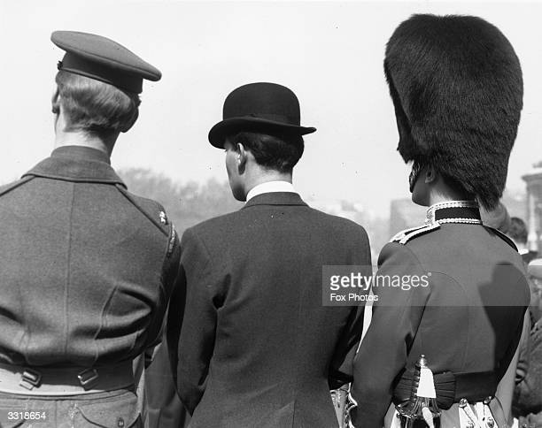 Men wearing a service hat, a bowler hat and a bearskin hat watch Guard Mountings at the Horse Guards Parade in London.