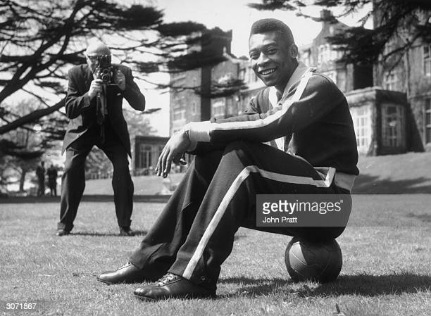 Star of the Brazilian football team Pele sits on the ball during a break in training at Selsdon Park Hotel where they are staying The Brazilians are...