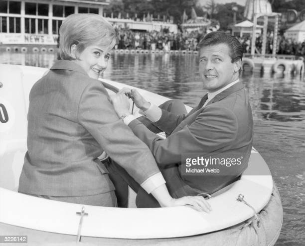 British actors Roger Moore and Liz Fraser take a ride on the boating lake at Festival Gardens in Battersea London Both are taking part in the annual...