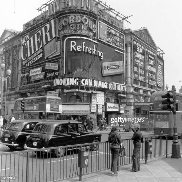 Two girls pointing at the signs in Piccadilly circus London which include an advertisement for Wrigley's Chewing gum and a Government health warning...