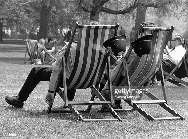 Two London policemen take the weight off their feet during the May heatwave whilst patrolling in the park