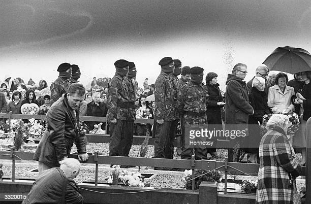 IRA members in combat jackets masks and berets at the burial of IRA hunger striker Bobby Sands MP in Belfast