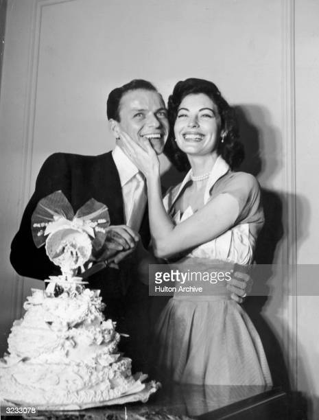 American pop singer Frank Sinatra poses with his wife American actor Ava Gardner standing behind their wedding cake on their wedding day Gardner...
