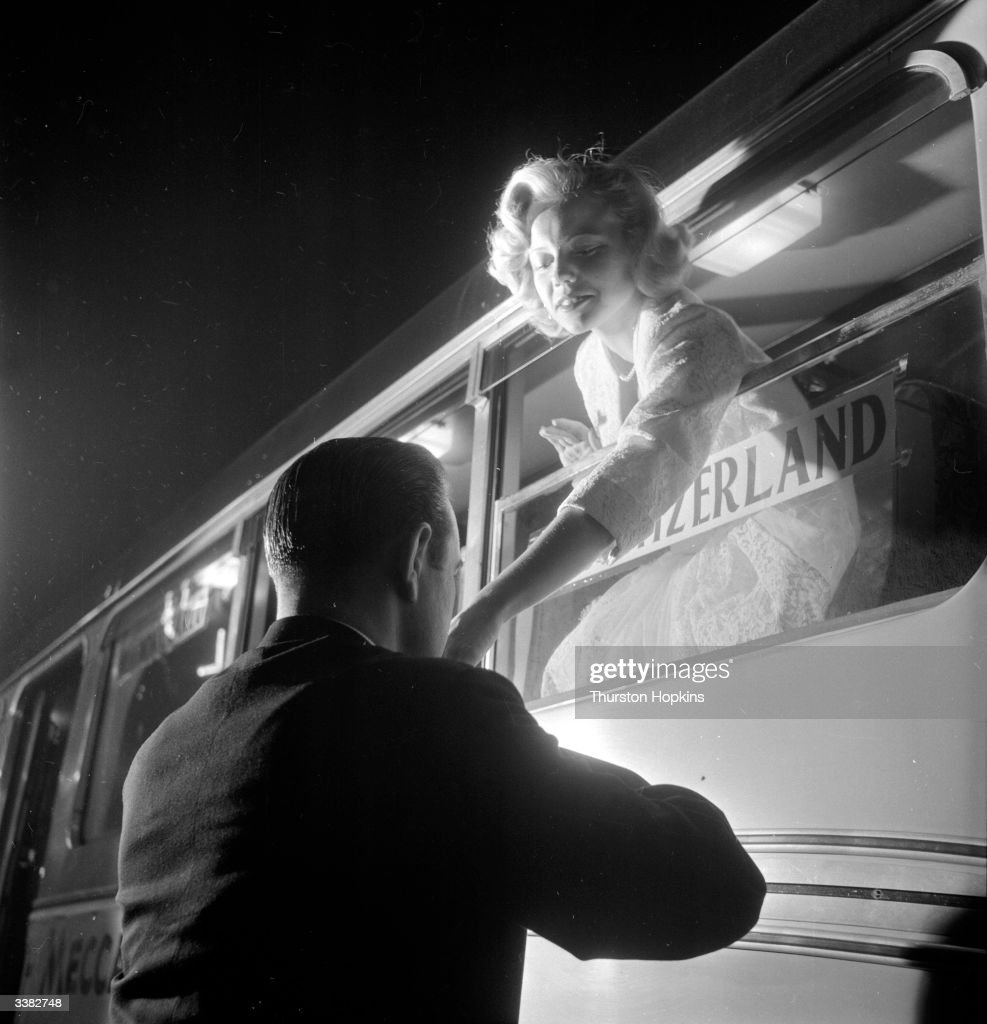 A contestant in a 'Miss World' beauty competition sponsored by Mecca Dancing, has her hand kissed by an admirer through a bus window. The bus called the 'Comet' was provided by BOAC to transport the contestants when they were in London. Original Publication: Picture Post - 6785 - The Beauty Contest Business - pub. 1953