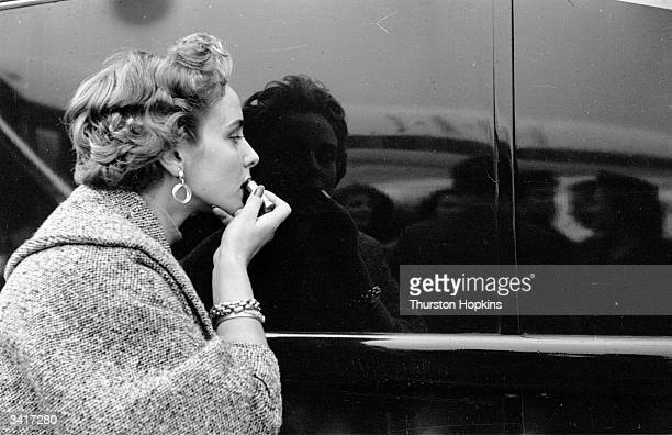 A contestant in a 'Miss World' beauty competition sponsored by Mecca Dancing applying her lipstick using a shiny car as a mirror Original Publication...