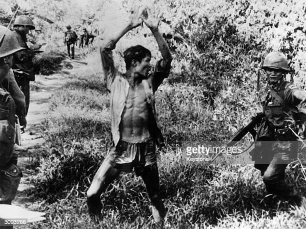 A Viet Cong suspect holds his hands up after a Vietnamese Ranger from the 21st Vietnam Infantry Division routed him from his hiding place