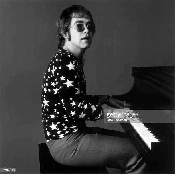 Portrait of British-born musician Elton John playing piano while wearing sunglasses and a shirt covered in stars.