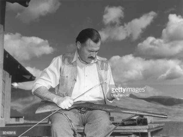 American writer Ernest Hemingway sits outdoors and cleans his Mannlicher rifle, a gun he first used during his African hunts, Idaho.