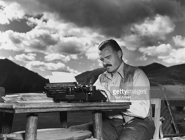 American writer Ernest Hemingway works at his typewriter while sitting outdoors, Idaho. Hemingway disapproved of this photograph saying, 'I don't...