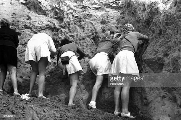 Tourists collecting sand in Alum Bay in the Isle of Wight. Original Publication: Picture Post - 241 - Hunters Of The Sand - pub. 1939