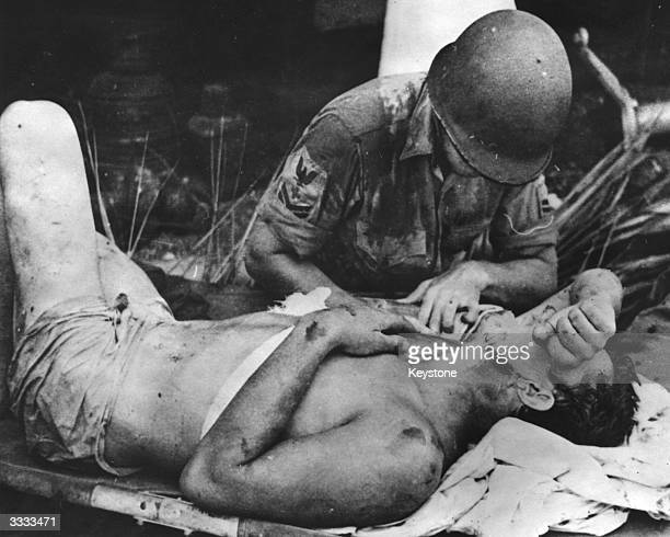 Navy pharmacist's mate dressing the wounds of an injured survivor from USS 'Calhoun', sunk during an early assault on Guadalcanal, the Solomon...