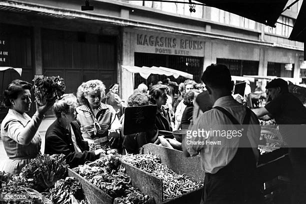 Shoppers buying produce at a Paris street market Original Publication Picture Post 5133 Sunday With Colette Ripert pub 1950