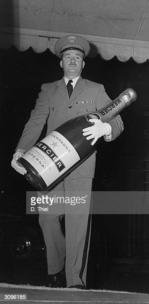 A methuselah of Mercier champagne being carried by a concierge at the Savoy hotel London