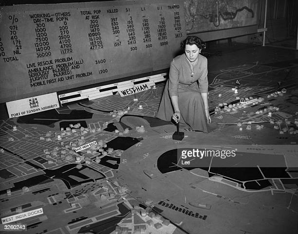Margaret Rowe a clerical officer in the Home Office Civil Defence Region studying a model of London's dock area as part of a Civil Defence exercise...