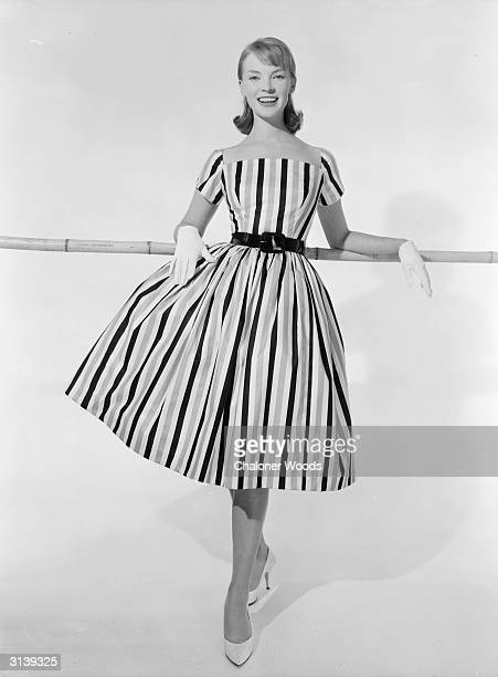 A carefree young miss models a square necked summer dress with short sleeves and full skirt made in a bold striped material A Brilkie design