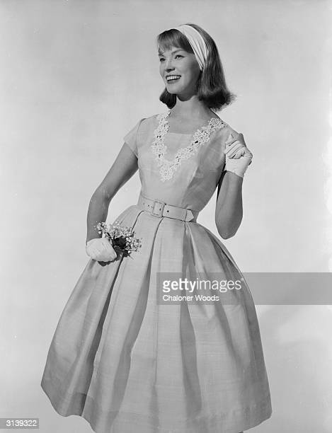 A prim young lady clasps a delicate corsage close to her summer dress which has a full skirt and short sleeves The square necked fitted bodice has an...