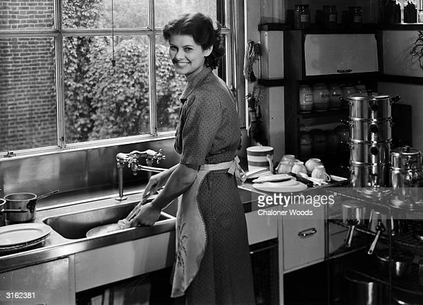 A smiling woman uses a dish mop to do the dishes
