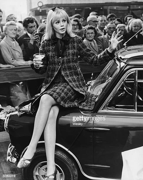 Actress Britt Ekland sitting on the Mini her husband Peter Sellers bought for her birthday at the Radford Motor Company showroom Hammersmith London