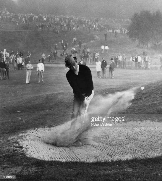 Lu Liang Huan, the Taiwanese golfer, known as 'Mr Lu' chops his ball out of the bunker creating a cloud of sand while playing in a match at Wentworth.