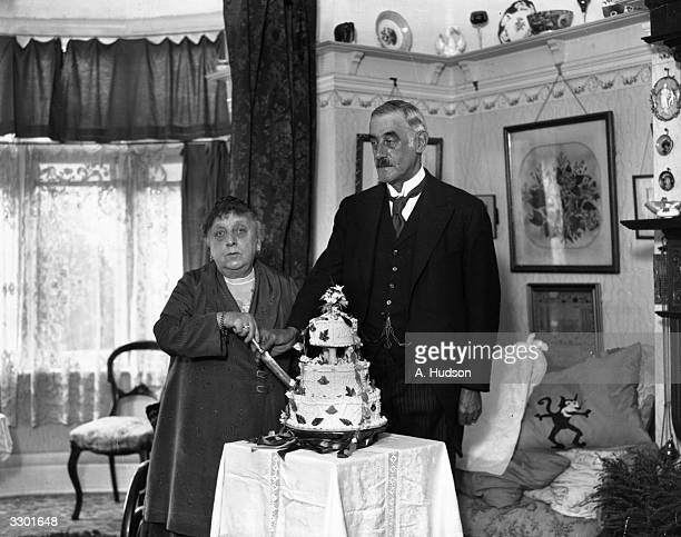 Mr W Knightsmith, a London toastmaster celebrating his golden wedding, cuts a cake with his wife.