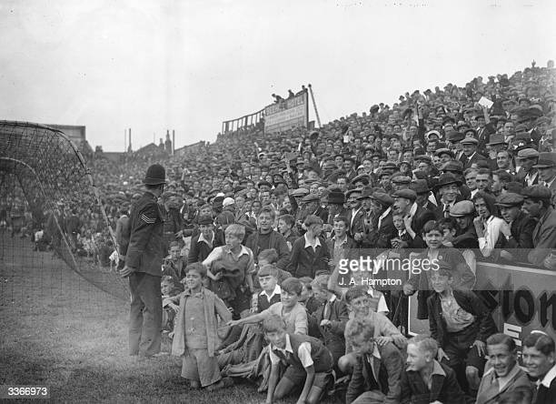 Children are allowed to sit on the sidelines of the pitch as Brentford play Huddersfield Town at Brentford