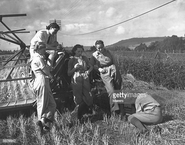 Members of the Women's Land Army pause from harvesting to listen to a radio news bulletin in a Monmouthshire field