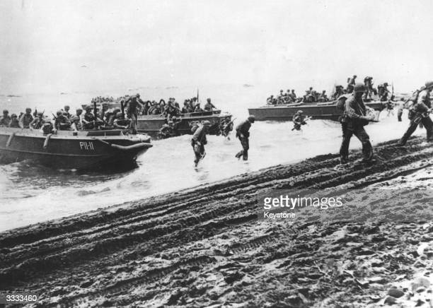 American marines landing from barges on a beach at Guadalcanal to begin an attack on the Japanese