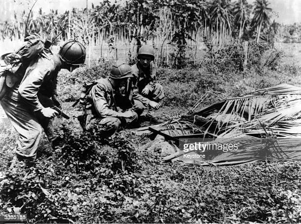 Marines examining a Japanese machine gun emplacement dug into the jungle floor at Guadalcanal.