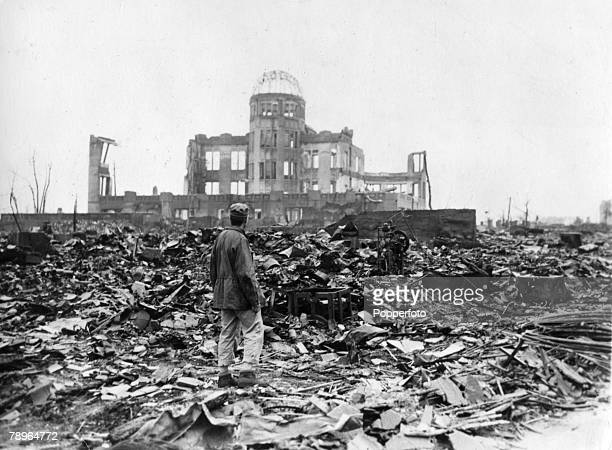 An Allied correspondent stands in the rubble, looking towards the ruins of the Hiroshima Prefectural Industrial Promotion Hall after the 6th August...