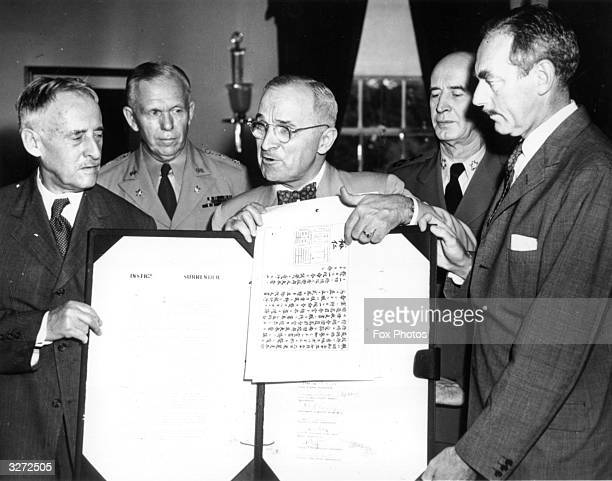 President Harry S Truman holding up the official Japanese document of surrender with Emperor Hirohito's signature at a White House meeting