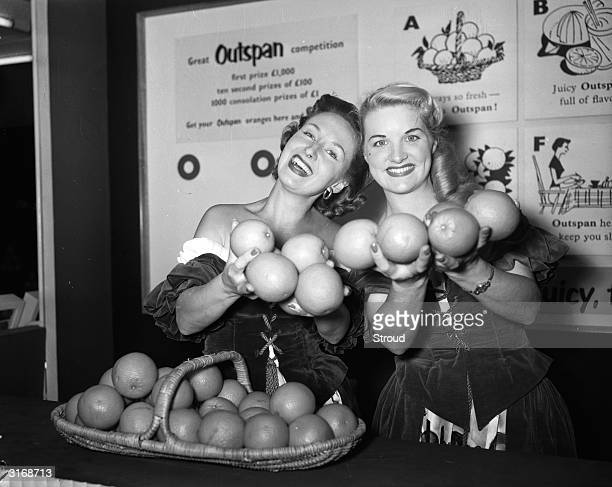 Elaine Williams and Lynn Stuart display oranges at a food fair on behalf of the Outspan company