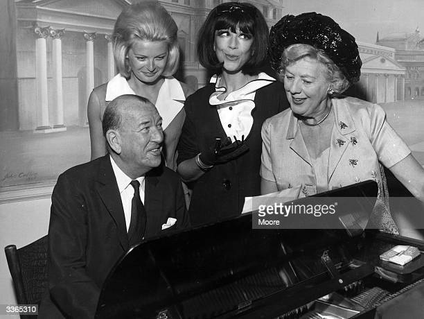 The stars of 'High Spirits' a musical comedy based on Noel Coward's play 'Blithe Spirit' gathered around the piano with the author for a song LR Noel...