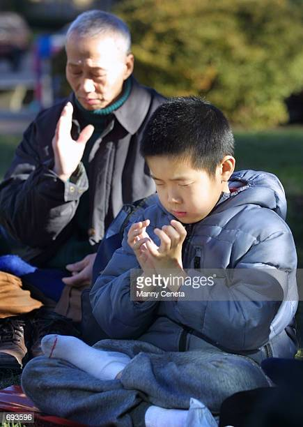 7yearold Alex Ting of Rockville MD meditates with other Falun Gong practitioners in front of the Chinese embassy January 12 2002 in Washington DC The...