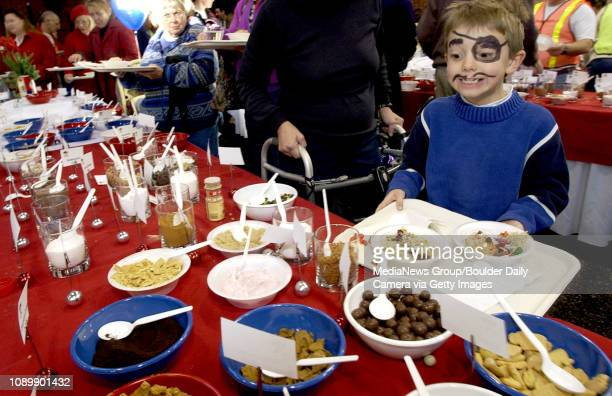 7yearold Austin Hurst of Boulder looks at the toppings table with amazement at the selection while sprucing up his bowl of oatmeal during Saturday...