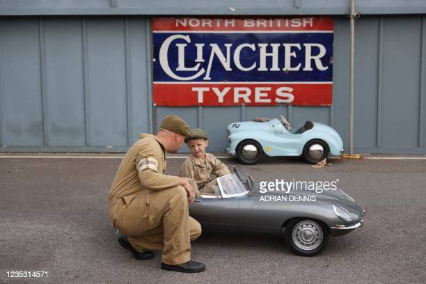 Year-old Hugo Upward and his father show off their miniature Jaguar E-type, a one-third, scale replica of a full sized car, at the Goodwood Revival...