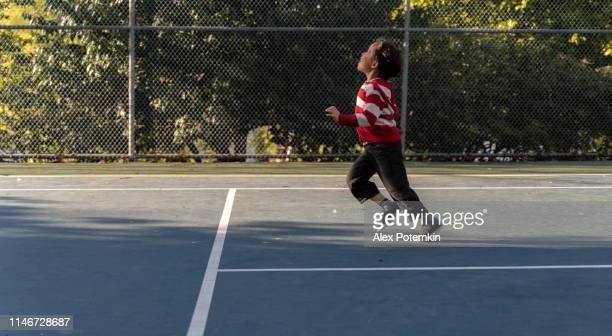 7-years-old boy playing on the tennis court in the park in the sunny warm spring day. - 6 7 years stock pictures, royalty-free photos & images