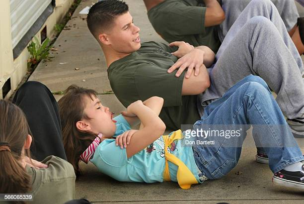 MARCH 2 2009 VISTA CA 7yrold Sadie StHolland struggles mightily to keep up as Marine Sgt Erik Halvorsen leads her 2d grade class in situps during a...