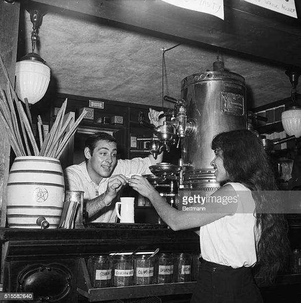 New York, NY: Beatniks in Greenwich Vilage. Photo shows man talking ton woman while giving her a cup of espresso at a coffee shop.