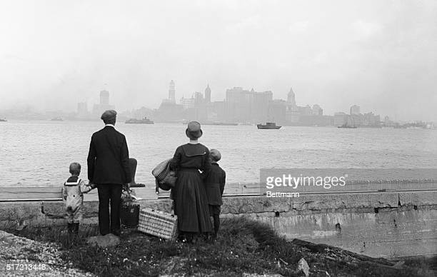 8/13/1925New York NY Above is a striking photo showing a little immigrant family on the dock at Ellis Island NY just having passed the rigid...