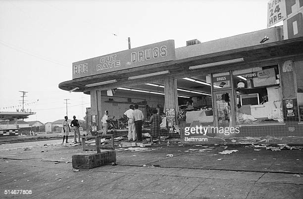 8/13/1965Los Angeles CA Negro residents of the Watts district look over damage early following the second night of wild rioting Molotov cocktails...