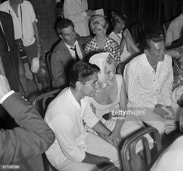 8/14/1958Antibes France French film star Brigitte Bardot holds hands with her vacation companion Sacha Distel at the wedding of jazz musician...