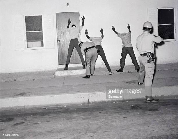 8/15/1965Long Beach CA Policeman at right holds gun on Negro rioters as a fellow officer searches the trio for weapons after one officer was killed...